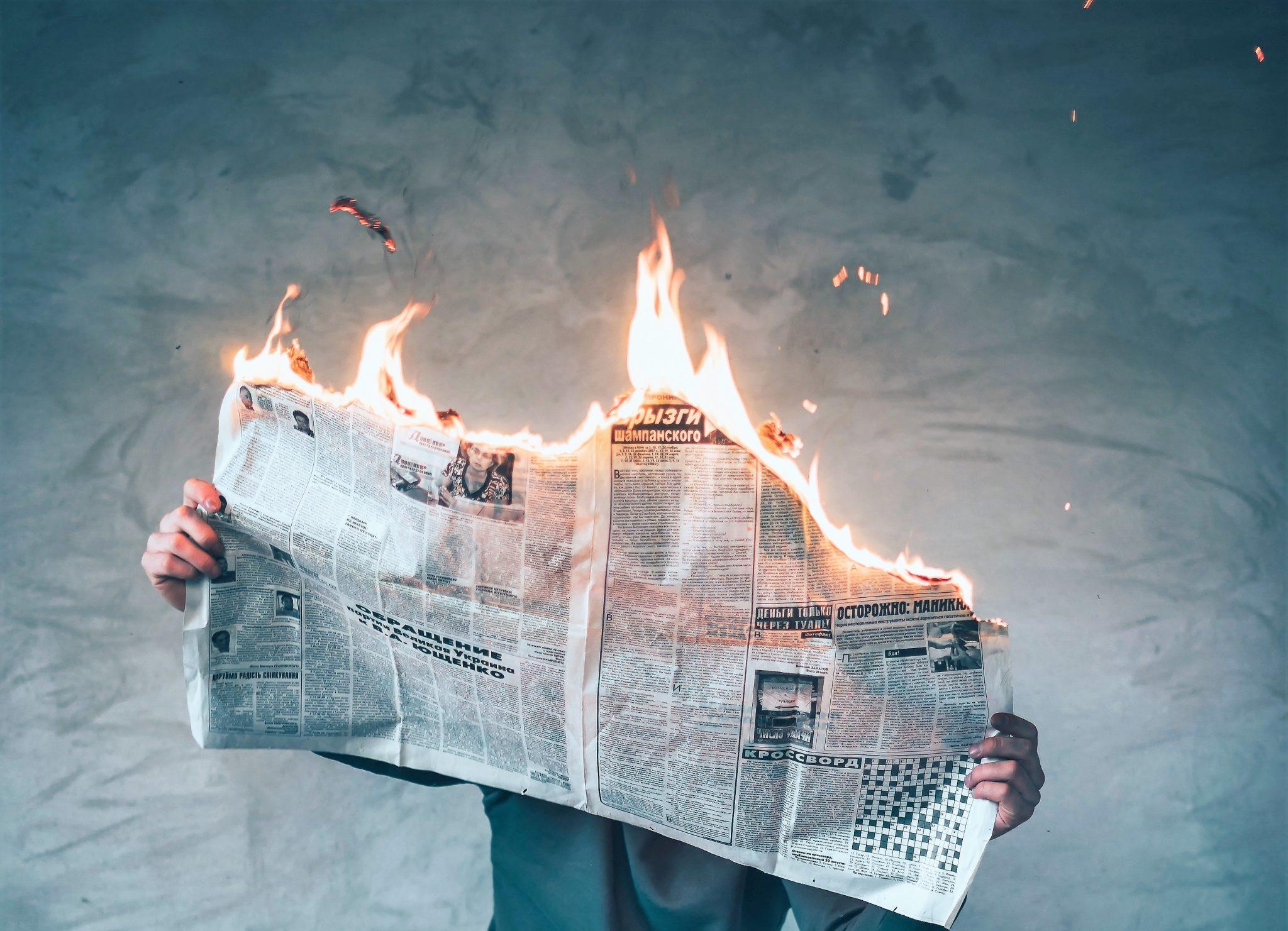 Leser mit brennender Zeitung in der Hand