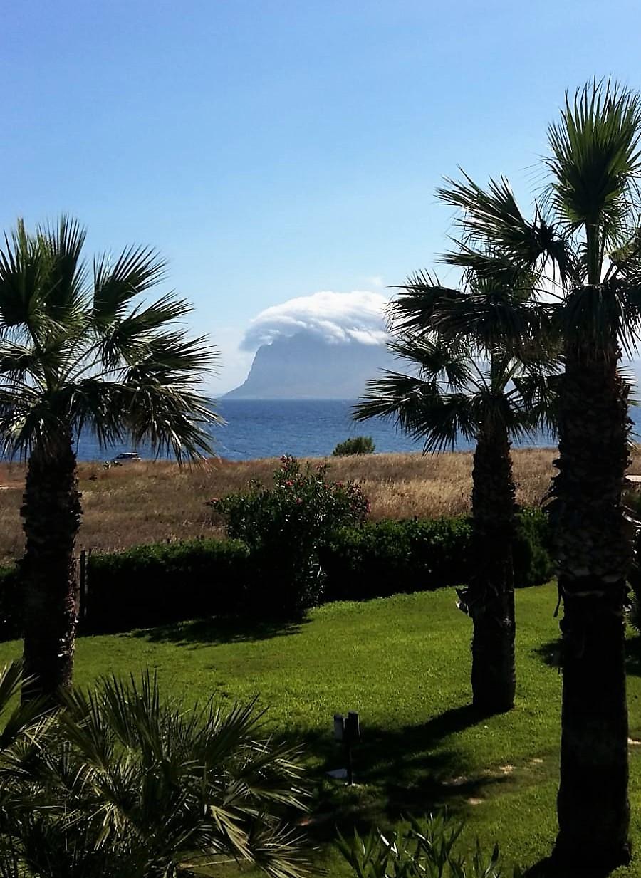 Blick einen Berg, Meer und Palmen in Sizilien