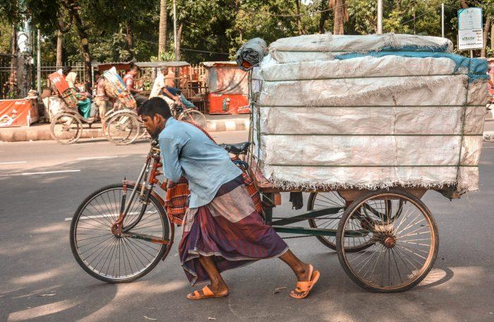 Radfahrer, der einen überladenen Anhänger zieht