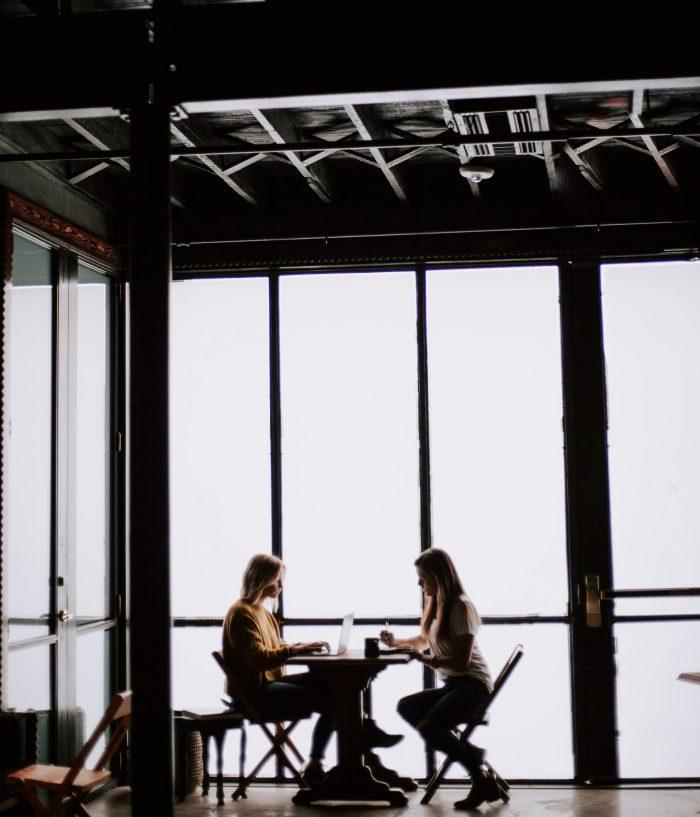 Schlechtes Gewissen loswerde: zwei Frauen beim Kaffeetrinken