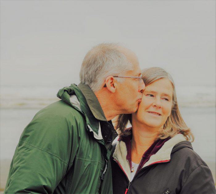 Schlechtes Gewissen loswerden: älteres Ehepaar beim Spaziergang. Mann küsst Frau auf die Wange, sie schaut lächelnd in die Ferne