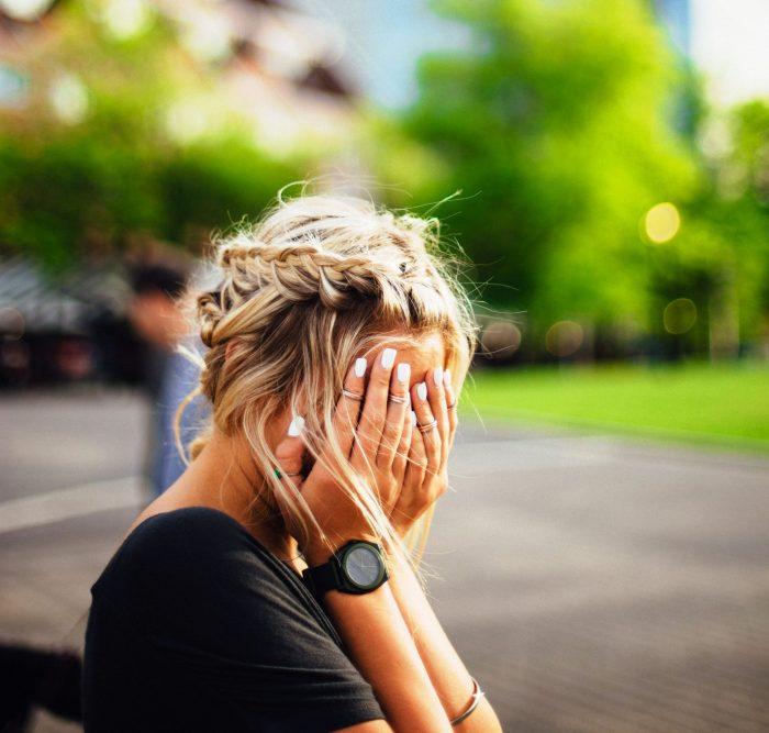 Kritik üben: Mädchen, das Hände vors Gesicht schlägt