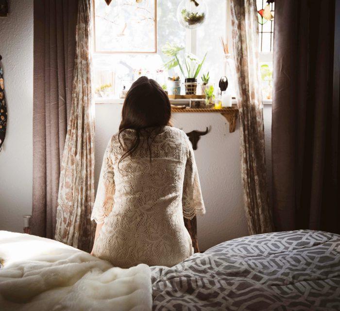 Schlechtes gewissen loswerden: Mädchen von hinten auf einem Bett sitzend