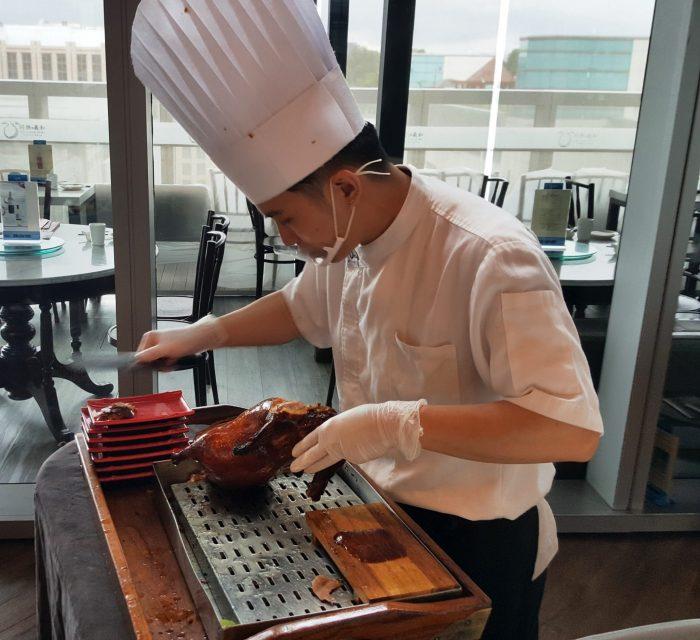 Koch, der eine Pekingente zerlegt