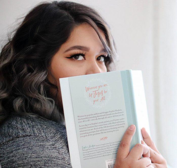 Frau, die sich hinter Buch versteckt