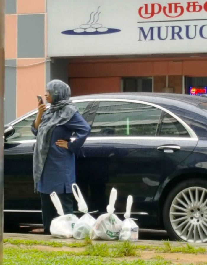 verschleierte Frau die mit Handy telefoniert, während vor ihr auf dem Boden viele Einkäufe in Plastiktüten stehen
