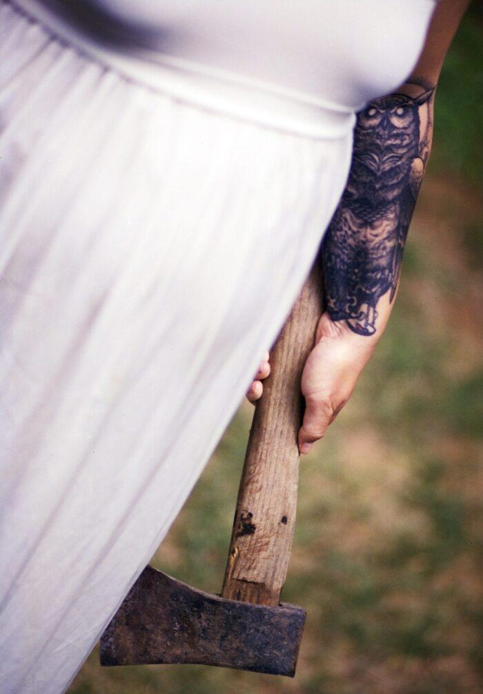 Frau mit Axt in der Hand und in einem weißen Kleid