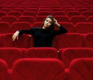 schwarzgekleidetes Mädchen in roten Kino-Plüschsesseln